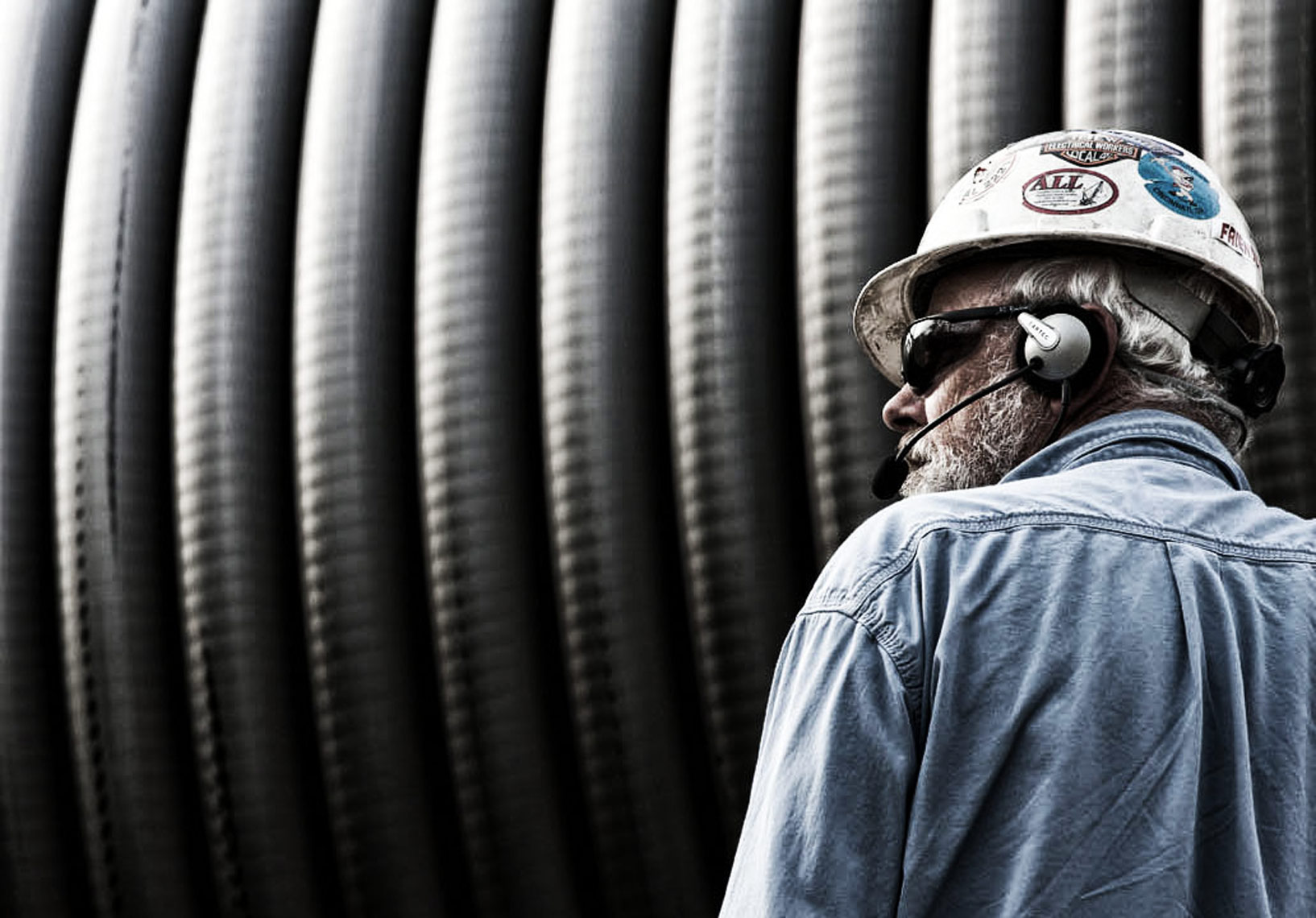 Industrial photo of man with large spool of cable